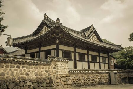 Hanok, a traditional Korean house behind a stone fence. Figured roof with tiles. Around the trees. Cloudy sky.  Muted tones, vintage toning.
