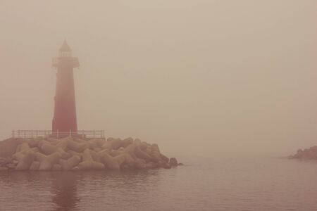 Red lighthouse at the entrance to the bay. Landmark, hazard warning. Everything is in thick fog. Around the sea, water. Фото со стока