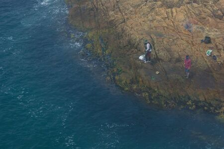 Deep blue sea, rocky coast. Two fishermen are fishing. Asian country. View from above.