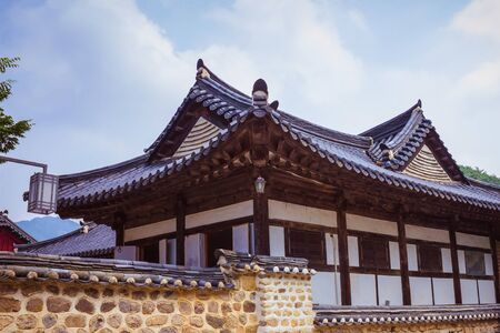 Large Korean house, traditional architecture. Figured roof with tiles. Natural stone fence, antique masonry. Blue sky, sunny lighting. Фото со стока