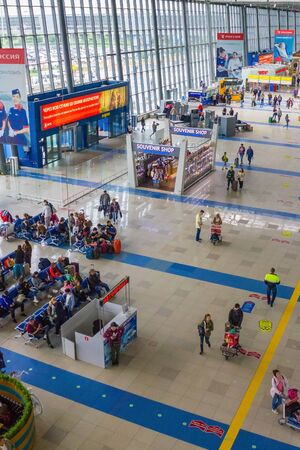 Vladivostok / Russia - 07/04/2019: Passenger air transportation, flights. Waiting room at the airport, top view. Passengers with luggage, gift shops. Daylight.