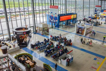 Vladivostok / Russia - 07/04/2019: Waiting room at the airport. Passengers with luggage, cafes, shops. Glass wall. View from above.