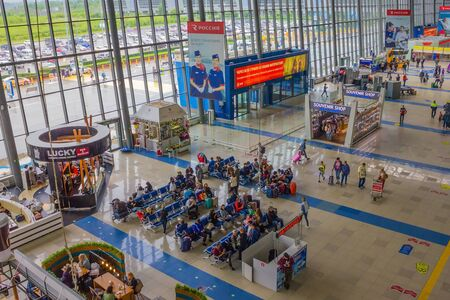 Vladivostok / Russia - 07/04/2019: Modern airport, air transportation. Transit, waiting room. People with luggage, cafes and shops. View from above.