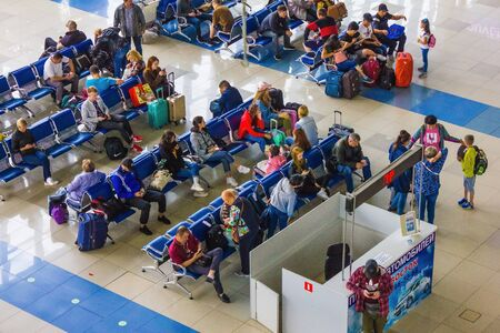 Vladivostok / Russia - 07/04/2019: Waiting for a flight at the international airport, transit, waiting room. Passengers with luggage, seats. Air transportation. View from above. Foto de archivo - 144178827