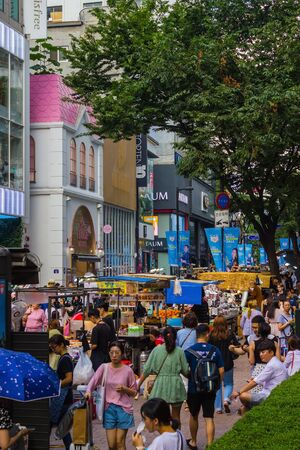 Seoul / South Korea - 07/29/2019: Shopping in Seoul, the capital of South Korea. Myeongdong, shopping district. Trays, street trading. Big shops. A lot of people, tourists.