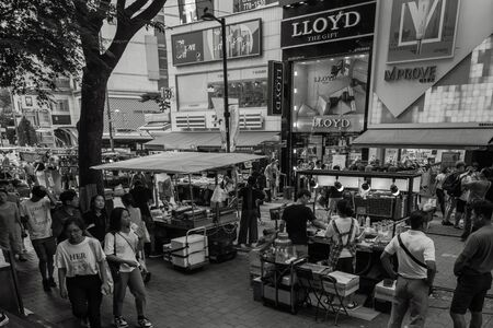 Seoul / South Korea - 07/29/2019: Shopping district in Seoul. Food stalls, street vendors, lots of tourists. Large signs, advertising. In black and white. Foto de archivo - 144178830