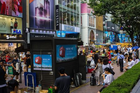 Seoul / South Korea - 07/29/2019: Shops, malls, street food stalls. Seoul shopping district. Tourists, busy street. Summer, early evening. Daylight.