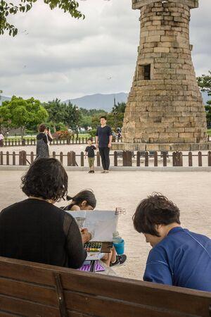 Gyeongju / South Korea - 07/07/2019: Cheomseongdae Observatory, Gyeongju neighborhood, park. Artists make drawings in their albums. Tourists take a photo. Summer day, cloudy.
