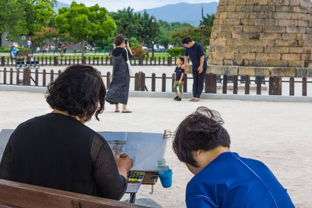 Gyeongju / South Korea - 07/07/2019: The artist draws sketches of  the Cheomseongdae Observatory. There are a lot of tourists around. History and culture of South Korea. Foto de archivo - 144178992