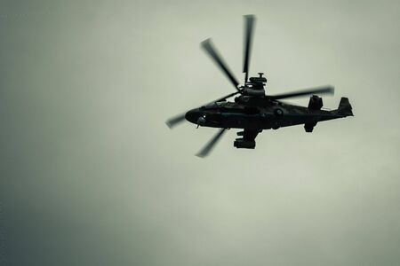 Helicopter flight in the background of thick clouds. Invasion, military operations, aggression from the air. Muted tones, vignetting. Stock fotó