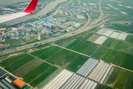 Airplane over the green fields. Asia, agricultural area. The wing is visible in the porthole. Muted tones, vignetting. Standard-Bild