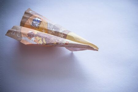 The plane is made from crumpled euro banknote. Airline losses, cheap flights, aircraft wear. Toning, vignetting.