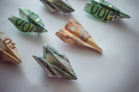 Paper airplanes made from euro and dollars. Flight delay, closing airlines, downtime. Light background, vignetting.