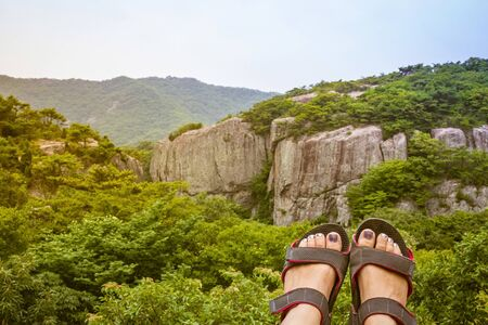 Women's feet in sports shoes on a background of green mountains. Traveling, hiking, active lifestyle. Summer day. Toning.