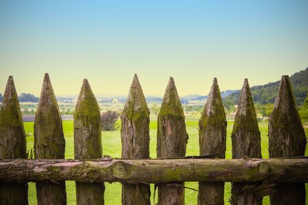 Fence made of natural logs. Thick stakes with sharp tops. Far away fields, green grass, hills. Restriction of freedom.