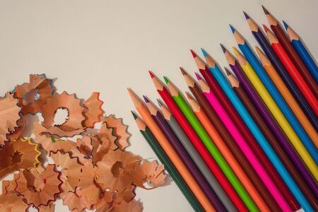 Many pencils of bright colors, a number of wooden shavings. Children's art, drawing, stationery.