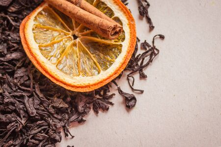 Dry black tea, large selective leaves, the highest grade. Near the orange and cinnamon. Additives for brewing, spices. Light background, copy space.