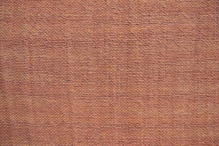 The homespun material, calm yellow and beige shades. Natural canvas, woven at home. Homogeneous background without a pattern.