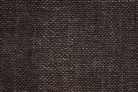 The texture of rough matting, linen fabric, home weaving. Large weaving, black and brown threads. A plain background without a pattern.
