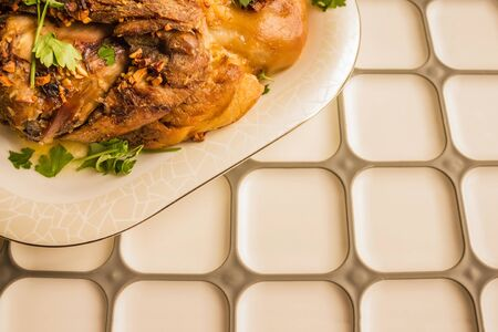 Hot meat dish, fried pork on a white plate. White kitchen table, copy space. Traditional homemade food. Warm toning.