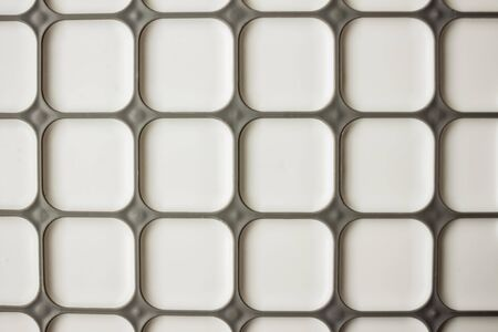 Geometric pattern, on a white background a gray grille. Large squares of the same size. Top view, daytime side lighting.