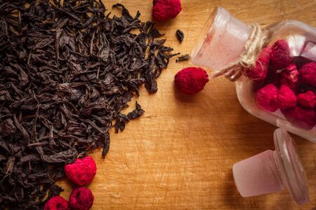 Black dry tea, selected leaves, on the kitchen board. Next, dried raspberries, flavor additive. Preparation of fruit tea, home comfort, hospitality. Banque d'images