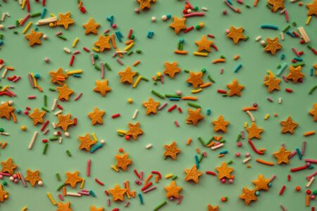 Cute children's background, asterisks and colored dragees. Mix, cheerful assortment, festive decor. Yellow toning, top view.