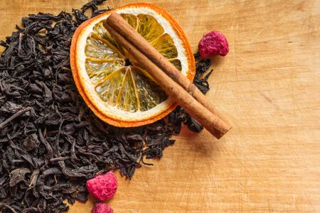Dry black tea, large leaves. Dried raspberries on top, a cinnamon stick, an orange circle. Aromatic additives to a traditional hot drink. Light wooden background, copy space.