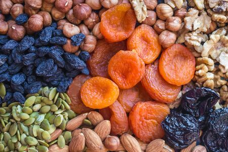 Dried apricots, nuts of different varieties and raisins. Useful, simple, satisfying, tasty food. Menu without meat, sources of vegetable protein. Top view, daylight.