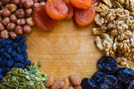 On the kitchen board, dried fruit and peeled nuts. Vegetarian cuisine, healthy lifestyle. A natural source of vegetable protein and vitamins.