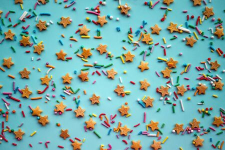 Cheerful children's background, festive mood, joy, happiness. On a blue surface, yellow stars, a multi-colored pellet, a mix. Birthday, fun.