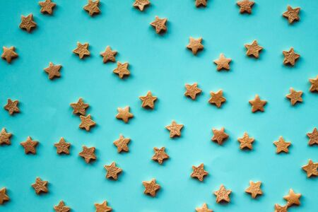 Gold stars on a calm blue background. Children's theme, abstraction. Daylight, top view. Foto de archivo
