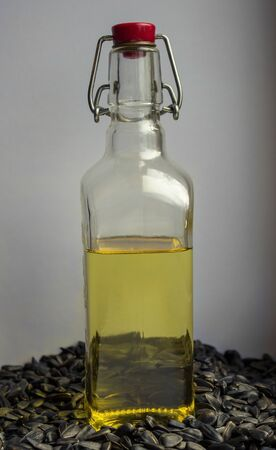On black seeds there is a glass bottle with sunflower oil. The yellow oil is poured up to half the capacity. Light gray uniform background. Vertical arrangement.