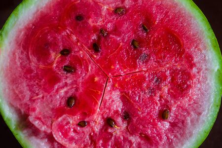 Round half of watermelon. Red pulp with brown seeds. View from above.