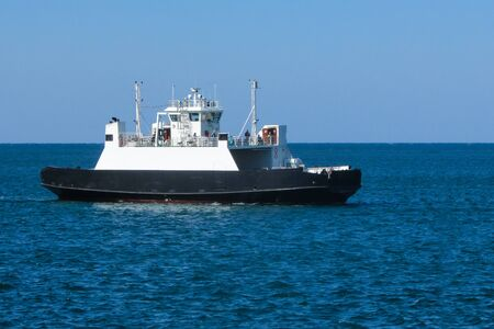 The cargo ferry in the blue sea. Clear sky. Transportation of goods and passengers. Side view. Skyline. Foto de archivo