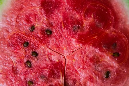 Juicy, ripe slice of watermelon with brown seeds. Bright, red, pink middle. View from above.