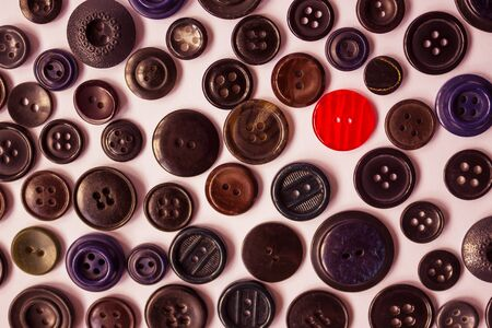 One red button on a background of dark vintage buttons for clothes. Bright individuality, dissimilarity, distinctive feature. View from above.