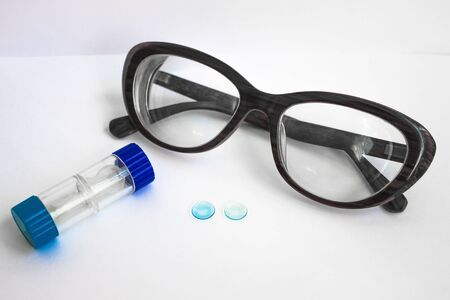 Modern correction of vision. On a white background, two blue contact lenses, a container for them, and thick glasses for a woman. View from above. Foto de archivo