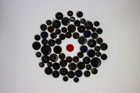 In the middle of the circle of different black buttons there is one red button. Difference from others, a bright personality among the gray world. Isolation, hostile environment, confrontation. White background, daylight. Foto de archivo - 143785933