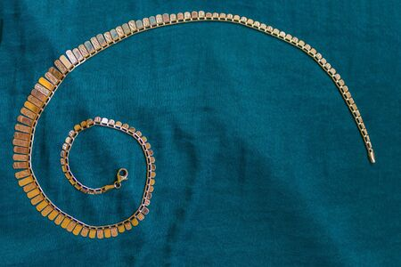 Women's necklace, coiled. Background of green natural silk. Jewelry of mass production. View from above.