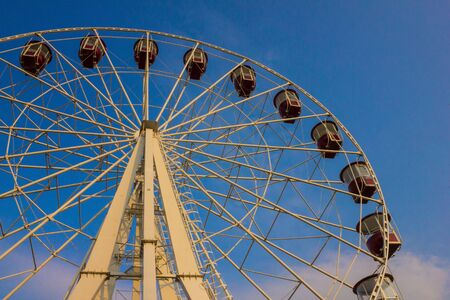 Against the background of blue, clear sky, a Ferris wheel with empty cabins. City entertainment, attraction. Bottom view.