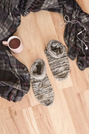 A conscious choice, a way out of the comfort zone, a craving for change of places. On the wooden floor there was a cozy plaid and comfortable socks. Nobody here. Foto de archivo