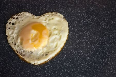 Scrambled eggs in the form of heart, burnt with passion. Killed by love. Dark background, vignetting.