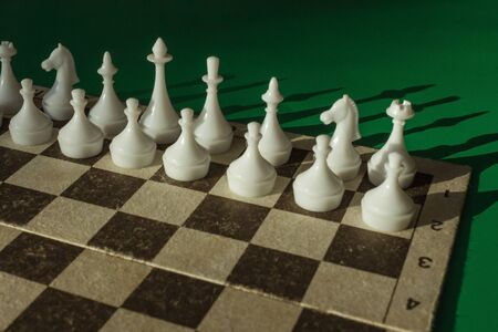 Old cardboard with chess pieces. White's position before the game, waiting for the first step. Daytime side lighting, green background.