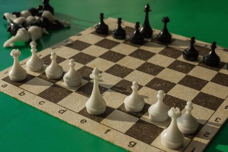 Pawns and figures on an old chessboard. Some of the pieces no longer participate in the game. Confrontation, battle, waiting for the next move.