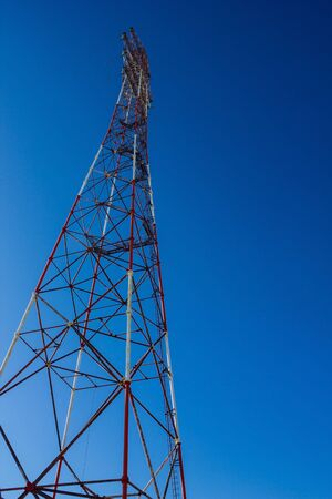 Against the backdrop of a bright blue sky, a power line tower. Power, supply of electricity. Vertical arrangement, view from below. Foto de archivo