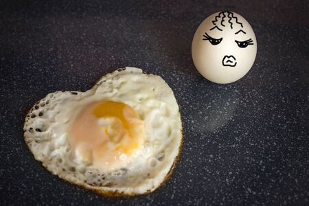 The scrambled egg in the form of a heart, the dude burned, died of love. The second egg does not share his feelings, it is indifferent. Hot heart and coldness. The picture is made by the author. Foto de archivo
