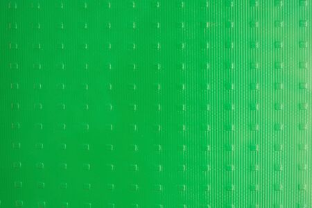 Glass surface, bright green color. Opaque texture. Daytime side lighting.