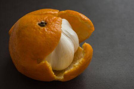 In the tangerine skin hides the bitter garlic. Deceived expectations, trickery, pretense. Dark background, side lighting.