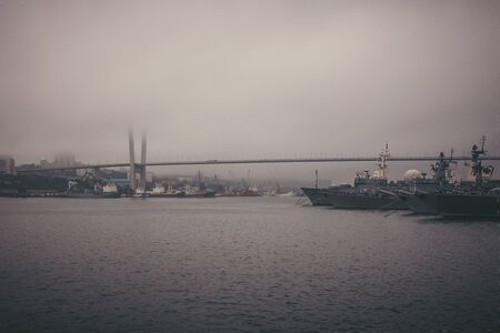 Vladivostok, port in the Pacific Ocean, Russia. Warships along the coast. Bridge over the bay. Vignetting, tinting, muted tones. Retro style. Foto de archivo